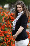 Happy pregnant woman in flowers expecting. Closeup on tummy of pregnant woman enjoying spring park, wearing black top and grey pants, holding in hands her belly Stock Images