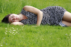 Happy pregnant woman on green grass Royalty Free Stock Image