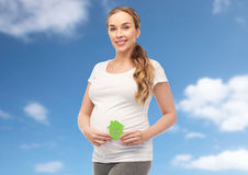 Happy pregnant woman with green house. Pregnancy, ecology, people and housing concept - happy pregnant woman with green house over blue sky and clouds background Stock Images