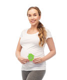Happy pregnant woman with green house. Pregnancy, ecology, people and housing concept - happy pregnant woman with green house over white background Stock Images