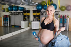 Happy pregnant woman at gym holding sport bag and bidon Royalty Free Stock Image