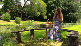 Happy pregnant woman have picnic on bench near river water
