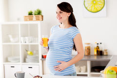 Happy pregnant woman having breakfast at home Stock Photo