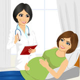 Happy pregnant woman having a doctor visit in hospital Stock Photography