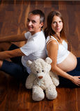 Happy pregnant woman with her husban on the floor Stock Images