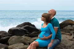 Happy pregnant woman and her husband on the coast. Stock Photos