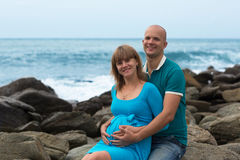 Happy pregnant woman and her husband on the coast. Stock Photography