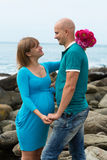 Happy pregnant woman and her husband on the coast. Stock Photo
