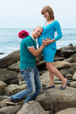 Happy pregnant woman and her husband on the coast. Royalty Free Stock Photo