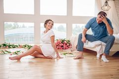 Happy pregnant woman with her husband are holding and listening to baby in belly and setting on living room`s floor at home, preg stock photo