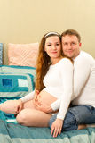 Happy pregnant woman and her husband at home on sofa. Royalty Free Stock Photography