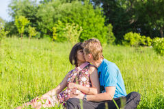 Happy pregnant woman and her husband kissing in the park. stock image