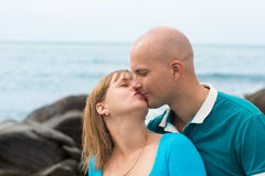 Happy pregnant woman and her husband kissing by the sea. Royalty Free Stock Photography