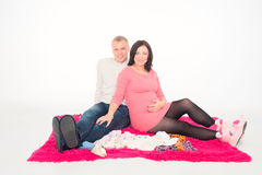 Happy pregnant woman with her husband looking at clothes for the Stock Photo