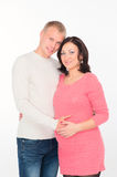 Happy pregnant woman with her husband looking at clothes for the Stock Photography