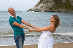 Happy pregnant woman and her husband strolling by sea. Stock Image