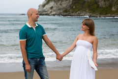 Happy pregnant woman and her husband strolling by sea. Royalty Free Stock Photo