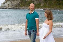 Happy pregnant woman and her husband strolling by sea. Royalty Free Stock Photos