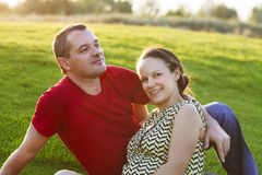 Happy pregnant woman with her husband at sunset Stock Images