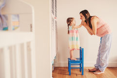 Happy pregnant woman with her toddler daughter at home royalty free stock photo