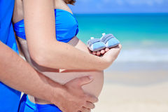 Happy pregnant woman holding baby shoes at beach Royalty Free Stock Photo