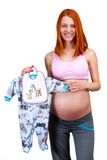 Happy pregnant woman, holding boy's dress Stock Photography