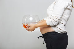 Happy pregnant woman holding a fishbowl with a goldfish in her h Stock Photos
