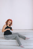Happy pregnant woman holding tummy booties, with a red bandage on his head. On a light background. Pregnancy red-haired. Young woman in a black t-shirt Stock Photography