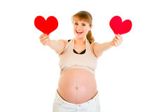 Happy pregnant woman holding two paper hearts. In hands isolated on white. Concept - two hearts beating in unison Stock Photography