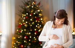 Happy pregnant woman at home on christmas stock images