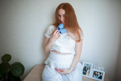 Happy pregnant woman at home holding a socks blue for baby. Happy pregnant woman in white clothes holding a blue socks for the baby Stock Image