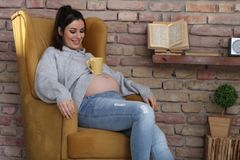 Happy pregnant woman at home relaxing in armchair Royalty Free Stock Photos