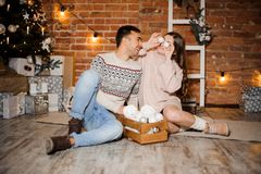 Happy pregnant woman with husband sitting near the Christmas tree and gift boxes. Happy pregnant women with husband in sweaters sitting near the Christmas tree Stock Images