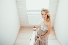 A happy pregnant woman. Interior. stairs stock photography