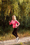 Happy pregnant woman jogging outside. Smiling expectant blonde running in forest. Sport, pregnancy, healthy lifestyle concept stock photo