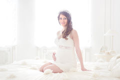 Happy pregnant woman in a light interior Royalty Free Stock Photos