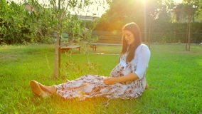 Happy pregnant woman listening music in park stock video footage