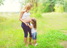 Happy pregnant woman, little child daughter kissing tummy mother Royalty Free Stock Image