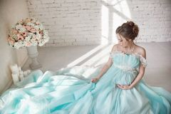 Happy Pregnant woman in long evening dress touching belly hands. Waiting the birth of a child, a woman in her eighth month Stock Image