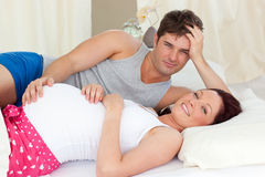 Happy pregnant woman lying on bed with her husband Stock Photo