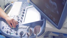 Happy pregnant woman is lying on a hospital bed and observing her ultrasound process. Pregnant woman is lying on a hospital bed and observing her ultrasound stock footage