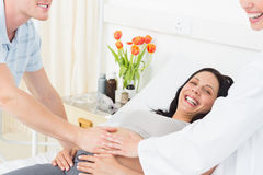 Happy pregnant woman with man and doctor Stock Image