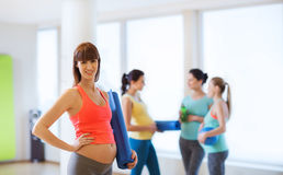 Happy pregnant woman with mat in gym Royalty Free Stock Photo
