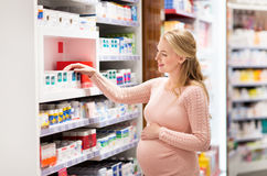 Happy pregnant woman with medication at pharmacy stock photo
