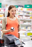 Happy pregnant woman with medication at pharmacy Royalty Free Stock Images