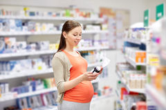 Happy pregnant woman with medication at pharmacy Stock Image