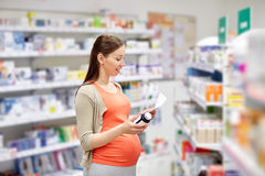 Happy pregnant woman with medication at pharmacy Royalty Free Stock Photos