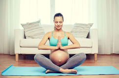 Happy pregnant woman meditating at home Royalty Free Stock Images