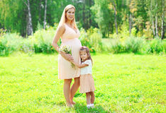 Happy pregnant woman, mother and little child daughter with chamomiles flowers Stock Images