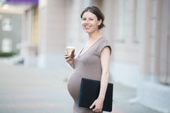 Happy pregnant woman office worker. Active mom. Portrait of happy young business pregnant woman looking at camera while standing on the street with document Stock Photo
